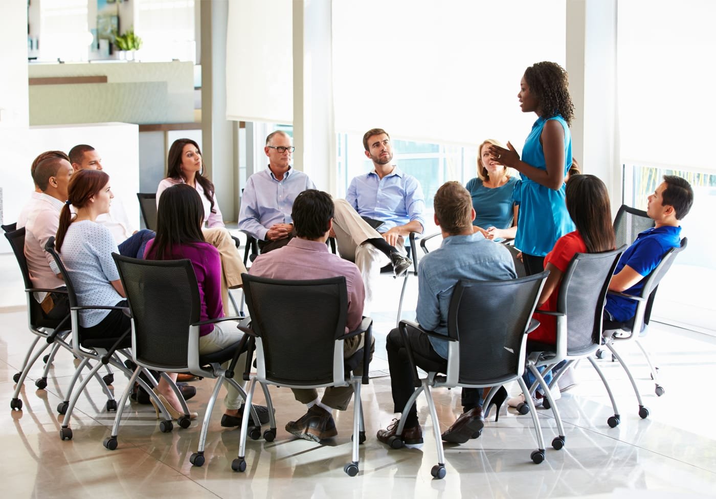 Businesswoman addressing multi-cultural office staff